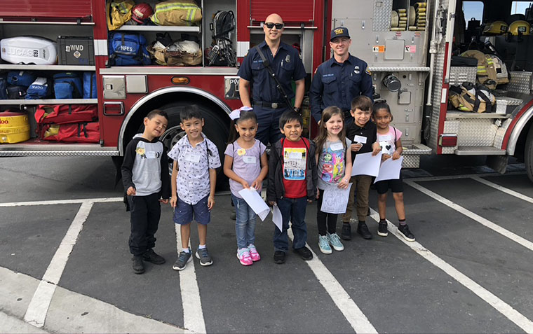kids with firemen in front of fire truck